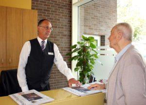 Älterer Mann redet mit Rezeptionist