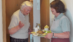 Ältere Dame bekommt ein Tablett mit Essen