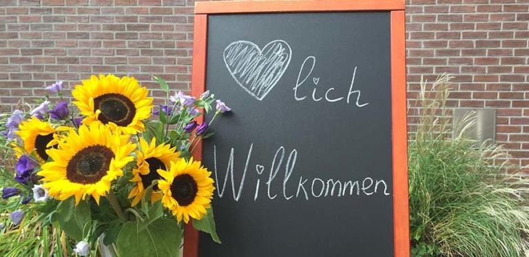 Herzlich Willkommen-Schild mit Sonnenblumen
