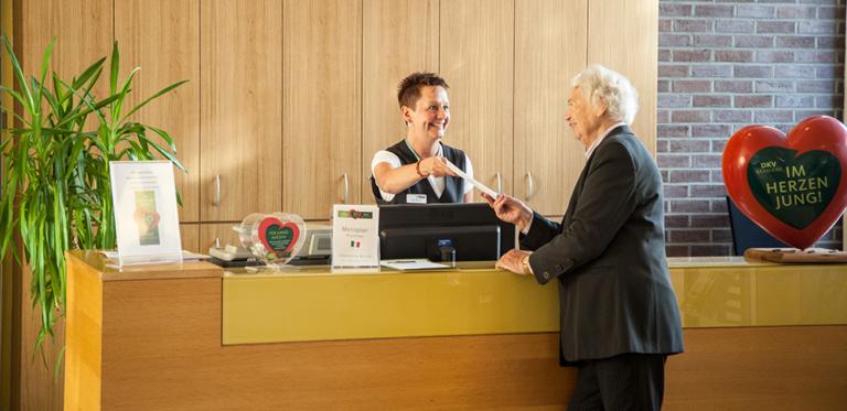 Frau reicht älteren Herren an der Rezeption eine Infobroschüre
