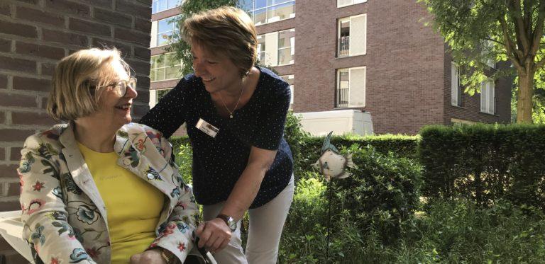 Pflegemitarbeiterin liest ältren Dame etwas aus der Zeitung or